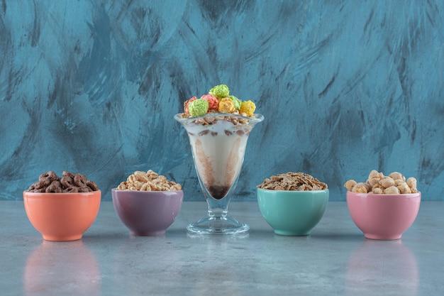 Cornflakes in einem milchkaffeeglas und in schalen, auf dem blauen tisch.