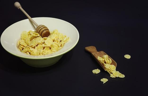 Cornflakes in einem teller. frühstück aus flocken mit honig und milch. schnelles frühstück mit cornflakes