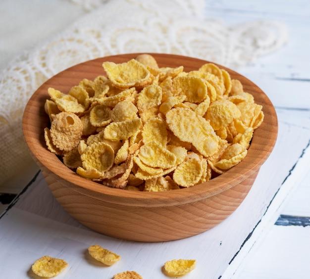 Cornflakes in einer braunen holzschale
