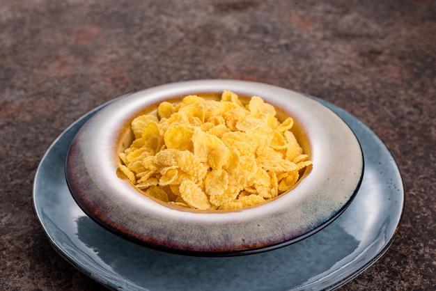 Cornflakes in einer keramikplatte auf einem dunklen hintergrund. frühstück.