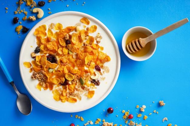 Cornflakes in einer schüssel mit milch und honig auf einem hellblauen hintergrund draufsicht