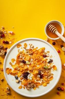 Cornflakes in einer schüssel mit milch und honig auf einem leuchtend gelben hintergrund draufsicht