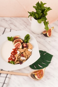 Cornflakes mit feigenfrucht und tadellosen blättern auf verzierter platte über marmorarbeitsplatte