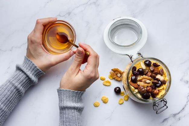 Cornflakes mit nüssen im glas. weibliche hände, die honig auf marmorhintergrund halten. draufsicht auf gesundes frühstück.