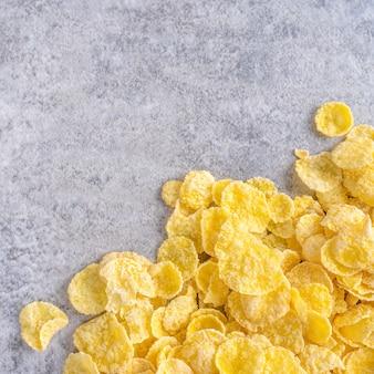 Cornflakes schüssel süßigkeiten auf grauem zement hintergrund, draufsicht flat lay layout design, frisches und gesundes frühstückskonzept.