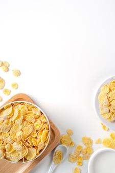 Cornflakes schüssel süßigkeiten mit milch und orange auf weißem hintergrund draufsicht flach lag überkopf layout frisch und gesund frühstück design-konzept