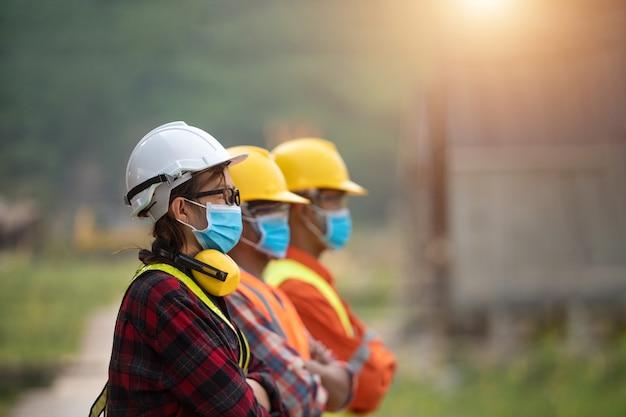 Corona oder covid-19 tragen während der bauplanung masken. neue normalität.das team der industrietechniker trägt eine covid-19-schutzmaske. arbeiter tragen eine quarantäne-gesichtsmaske.