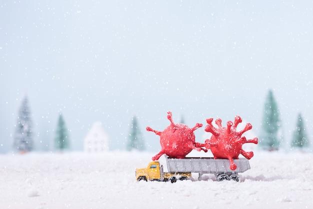 Corona-virus (covid-19), das durch formen von ton gebaut wurde, der auf spielzeugauto-lkw gemalt wurde, lief durch den schnee im feldweihnachtsbaum des natürlichen landschaftshintergrunds.