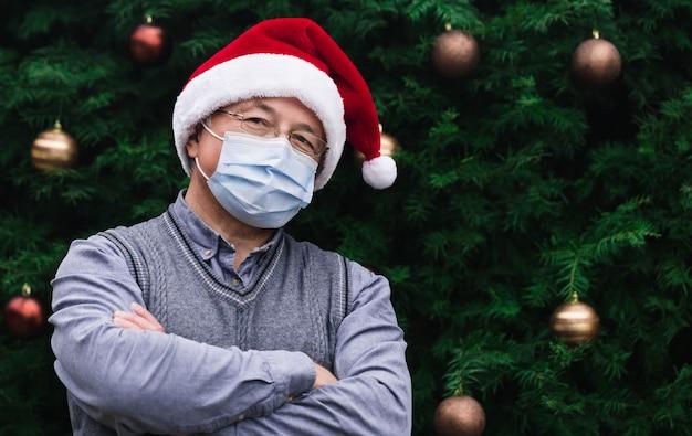 Corona weihnachten. schließen sie herauf porträt des älteren mannes, der einen weihnachtsmannhut und eine medizinische maske mit emotion trägt. vor dem hintergrund eines weihnachtsbaumes. coronavirus pandemie