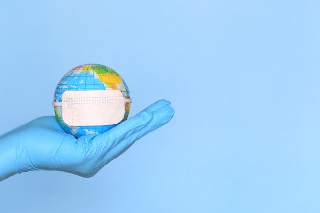 Coronavirus 2019-ncov, arzthand, die welt oder erde mit dem tragen der medizinischen schutzmaske auf blauem hintergrund, gesundheits- und sicherheitskonzept hält