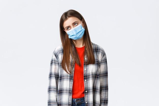 Coronavirus-ausbruch, freizeit in quarantäne, konzept der sozialen distanzierung und emotionen. düster und gelangweilt, traurige junge frau in medizinischer maske, seufzend, zögerlich wegschauen, satt zu hause sitzen.