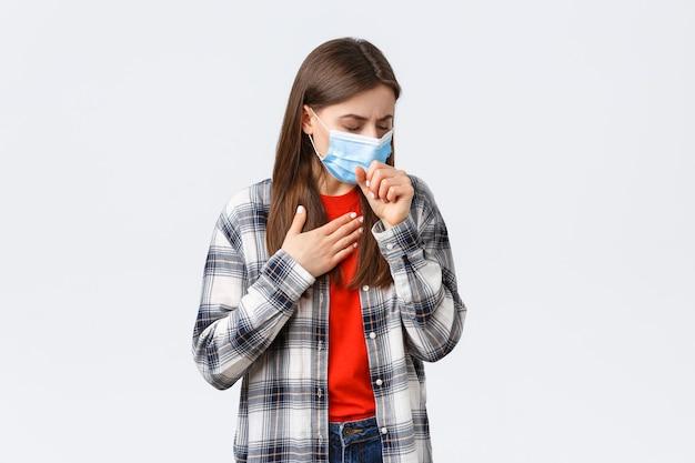 Coronavirus-ausbruch, freizeit in quarantäne, konzept der sozialen distanzierung und emotionen. frau in medizinischer maske, die hustet, sich krank fühlt, die lunge berührt, covid-19-symptome hat und krank ist.