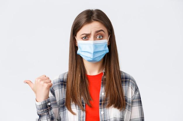 Coronavirus-ausbruch, freizeit in quarantäne, konzept der sozialen distanzierung und emotionen. skeptische junge frau in medizinischer maske drückt ihren unglauben gegenüber dem banner nach links aus und zeigt zweifelhaft