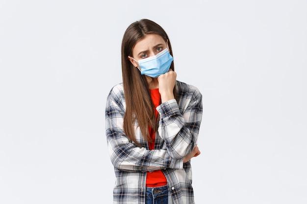 Coronavirus-ausbruch, freizeit in quarantäne, konzept der sozialen distanzierung und emotionen. trauriges und gelangweiltes junges düsteres mädchen in medizinischer maske lehnte sich an die hand und schaute unglücklich in die kamera