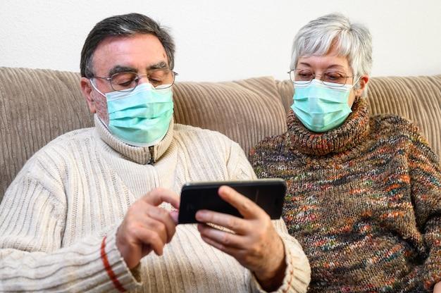 Coronavirus. bleib zu hause, lebensstil. fröhliches älteres ehepaar, das zu hause auf einem sofa in einer quarantäne sitzt und mit dem smartphone einen videoanruf tätigt. älteres paar mit schutzmasken.