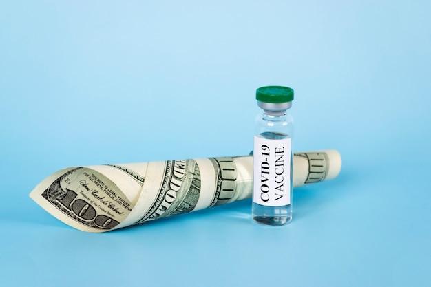 Coronavirus covid-19 impfglas, spritze und geld auf blauem hintergrund.