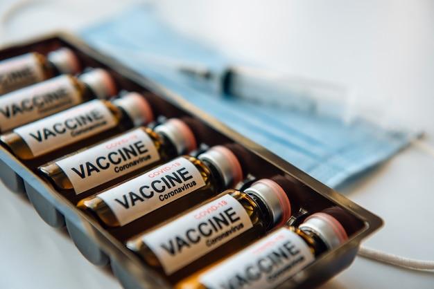 Coronavirus covid-19-impfstoffampullen in einer schachtel, unscharfer hintergrund, nahaufnahme. fläschchen mit medikament, etikett, spritze, medizinischer maske, selektiver fokus.