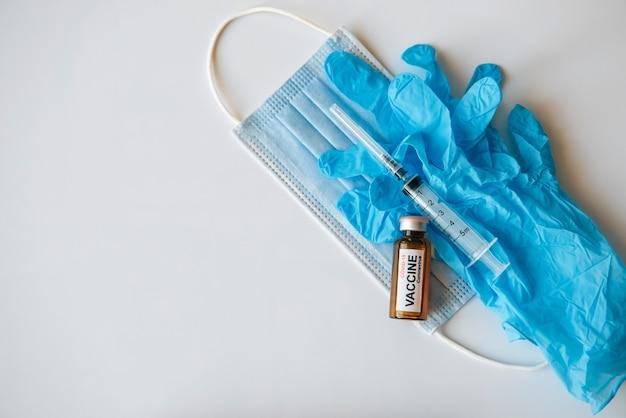 Coronavirus covid 19 impfstoffflasche und spritze auf medizinischer gesichtsmaske und blauen handschuhen