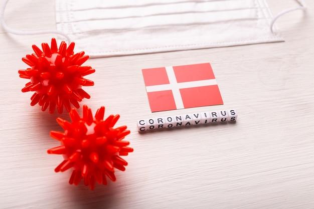 Coronavirus-covid-19-konzept. draufsicht atemschutzmaske und flagge von dänemark