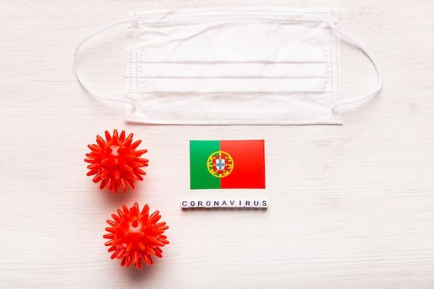 Coronavirus-covid-19-konzept. draufsicht schützende atemmaske und flagge von portugal. neuartiger ausbruch des chinesischen coronavirus.