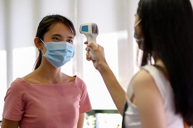 Coronavirus covid-19-konzept, frau, die maske mit thermoscan- oder thermometerpistolen trägt, die auf coronavirus prüfen
