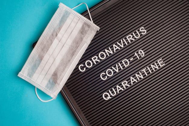 Coronavirus - covid -19 quarantäne - text auf schwarzem briefbrett und chirurgischer maske.