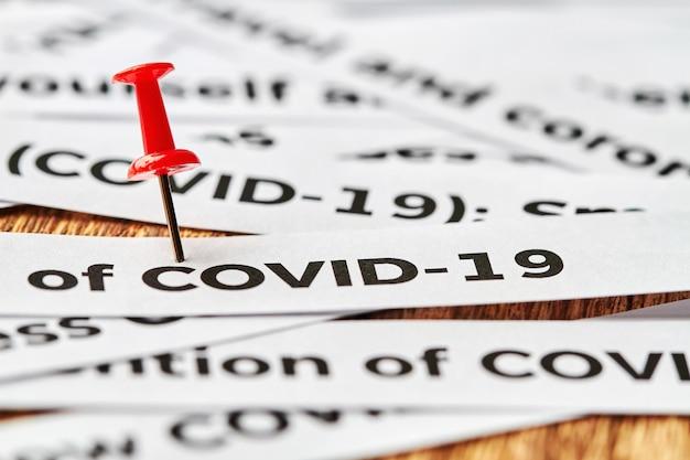 Coronavirus, covid-19, zeitungsausschnitte mit roter reißzwecke, die covid-19 kennzeichneten. konzept von covid-19. nahaufnahme, selektiver fokus