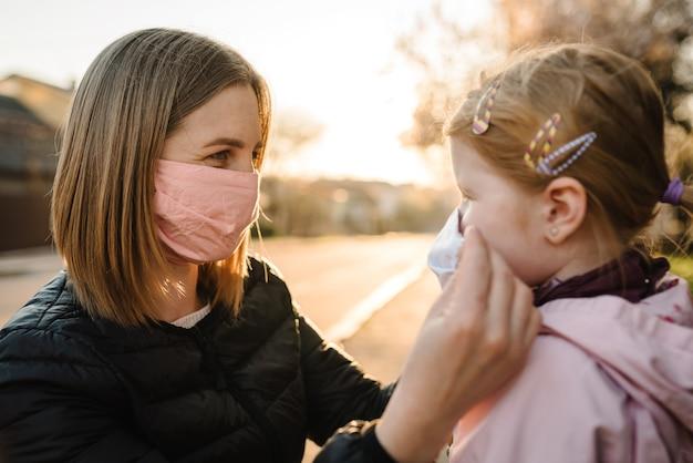 Coronavirus das endkonzept. nie mehr covid-19. kleines mädchen, mutter tragen masken gehen auf der straße. mutter entfernt maske glückliches kind. familie mit kind im freien. erfolg feiern. die pandemie ist vorbei, ist beendet.