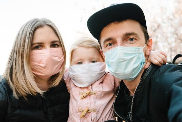 Coronavirus das endkonzept, viruskrankheit. gesunde familie mit kind in der medizinischen schutzmaske auf der straße. gesundheitsschutz und prävention bei grippe und infektiösem ausbruch. nie mehr covid-19.