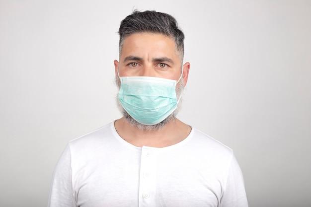 Coronavirus, ein mann mit einer medizinischen maske auf einem weißen hintergrund. titel zum ausbruch des kronenvirus, krankheit. epidemie