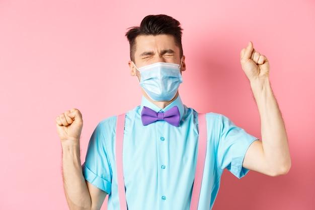 Coronavirus-, gesundheits- und quarantänekonzept. frustrierter mann in der medizinischen maske, die sich beschwert, hände schüttelt und versagen weint und über rosa hintergrund steht.