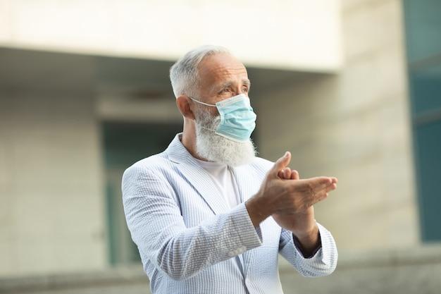 Coronavirus. hände mit desinfektionsspray in der stadt reinigen