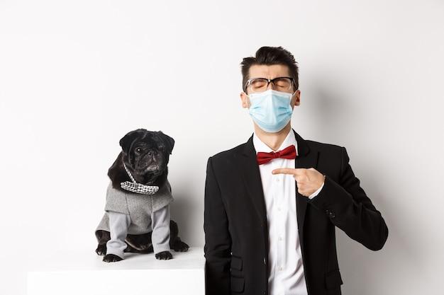 Coronavirus, haustiere und feierkonzept. enttäuschter junger mann in gesichtsmaske und anzug, finger auf niedlichen schwarzen mops-hund tragend partykostüm zeigend, über weiß stehend.