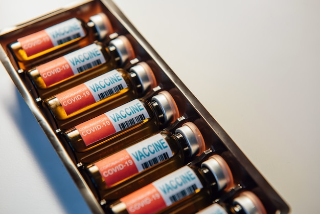 Coronavirus-impfstoff im paket, nahaufnahme. fläschchen mit medikamenten für covid19 liegen in einer reihe, weißer hintergrund, kopienraum. fokus auf etikett mit aufschrift.
