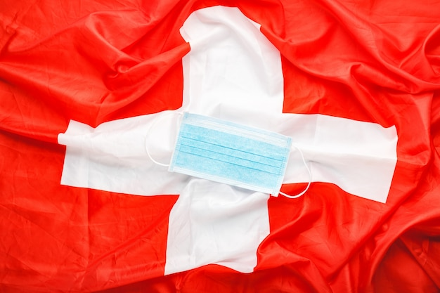 Coronavirus in der schweiz. chirurgische gesichtsschutzmaske auf schweizer nationalflagge. schweizer quarantäne, schutz coronavirus symbol des türkischen arztes, der krankenschwester, des medizinischen arbeiters. medizin gesundheitswesen.covid-19