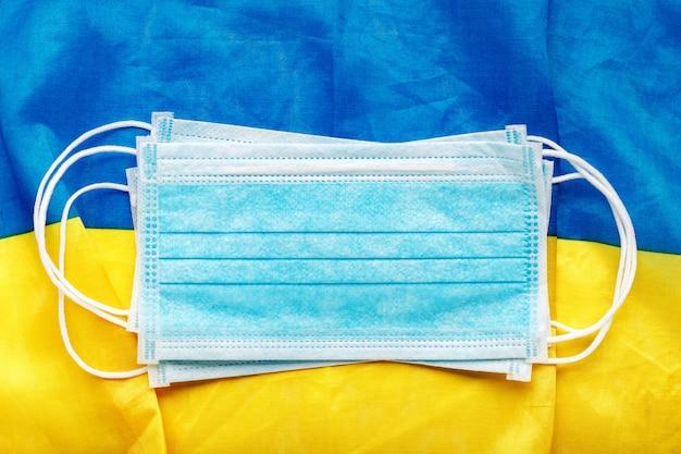 Coronavirus in der ukraine. chirurgische gesichtsschutzmaske auf ukrainischer nationalflagge. ukraine quarantäne, schutz coronavirus symbol von arzt, krankenschwester, medizinischem arbeiter. medizin gesundheitswesen. covid-19