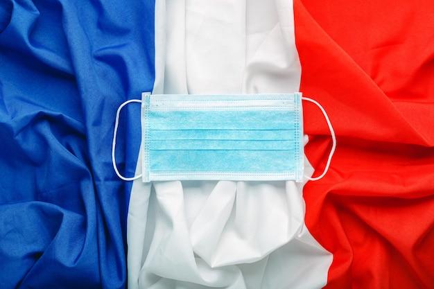 Coronavirus in frankreich. chirurgische gesichtsschutzmaske auf frankreich-nationalflagge. französische quarantäne, coronavirus-schutzsymbol des französischen arztes, der krankenschwester, des medizinischen arbeiters. medizinische gesundheitsversorgung. covid-19