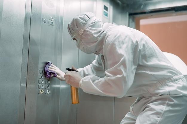 Coronavirus infektion. sanitäter in schutzmaske und kostüm desinfiziert einen aufzug mit sprühgerät,
