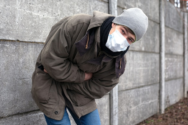 Coronavirus-infizierter mann mit medizinischer gesichtsmaske verliert das bewusstsein und wurde krank. infiziert mit dem neuen tödlichen chinesischen virus ncov-2019.