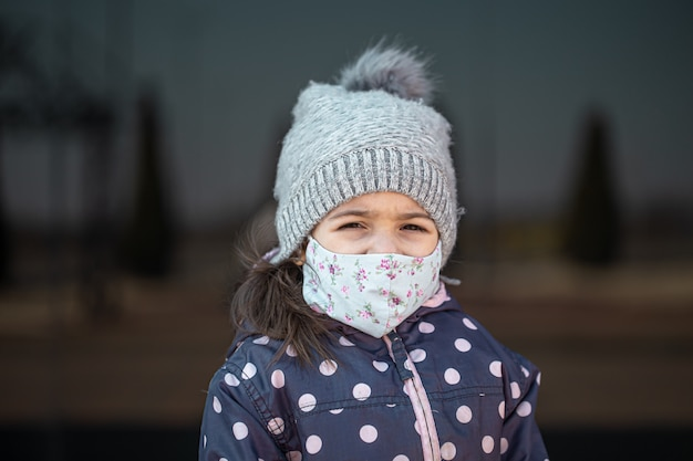 Coronavirus-konzept. ein kleines mädchen trägt während einer virusepidemie eine maske im gesicht