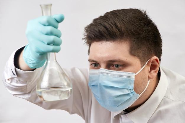 Coronavirus-konzeptmann in der medizinischen maske, die flasche in auf weißer wand betrachtet