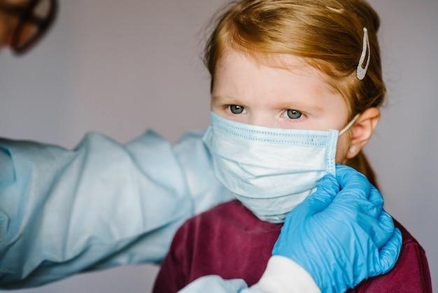 Coronavirus. krankenschwester, arzt im schutzanzug, trägt eine medizinische maske im gesicht für das kind. vorbeugende maßnahmen gegen covid-19-infektion. konzept des schutzes gegen influenza, corona-virus-epidemie.