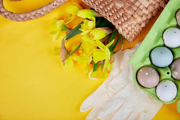 Coronavirus ostersymbol eier und narzissenblüten im korb nahe medizinischen schutzhandschuhen