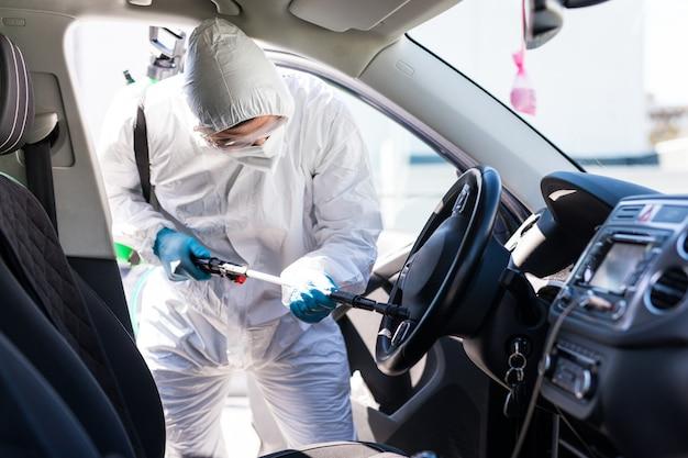 Coronavirus pandemie. desinfektor in einem schutzanzug und maske sprüht desinfektionsmittel des autos im freien