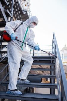 Coronavirus pandemie. ein desinfektionsmittel in einem schutzanzug und einer maske sprüht desinfektionsmittel in den raum.