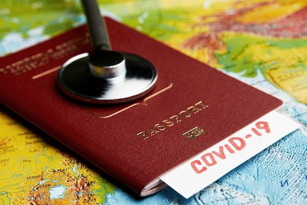 Coronavirus-pandemie-reisekonzept. covid-19 medizinischer test. covid 19 reisedokument auf weltkartenhintergrund mit reisepass und medizinischem stethoskop