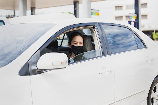 Coronavirus-pandemiekonzeptfrau mit schutzmaske sitzen in einer auto-straßenfahrtreise.