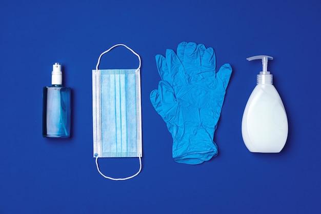Coronavirus prävention. gesichtsmaske, handschuhe, seife und desinfektionsmittel auf blau