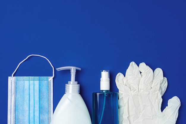 Coronavirus prävention. gesichtsmaske, handschuhe, seife und desinfektionsmittel auf blauem hintergrund