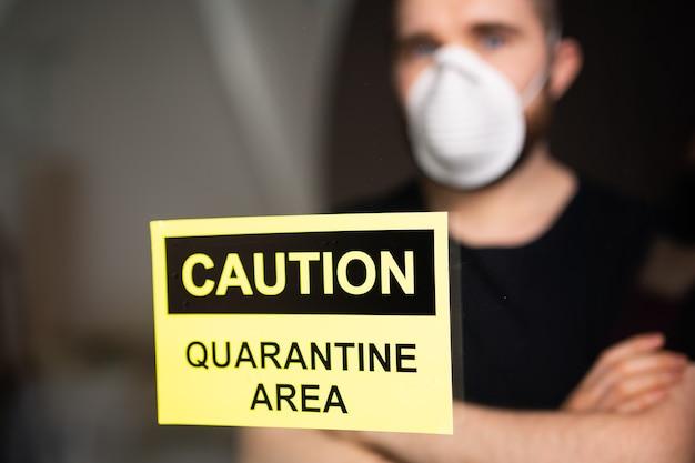 Coronavirus-, quarantäne-, covid-19- und pandemiekonzept. trauriger und kranker mann des koronavirus, der durch das fenster schaut